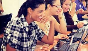 Imagem mostra pessoas mexendo em computadores
